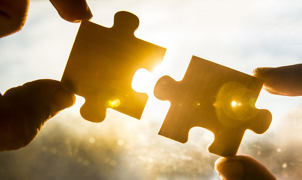 Zwei Haende mit je einem Puzzleteil, welche zusammen passen