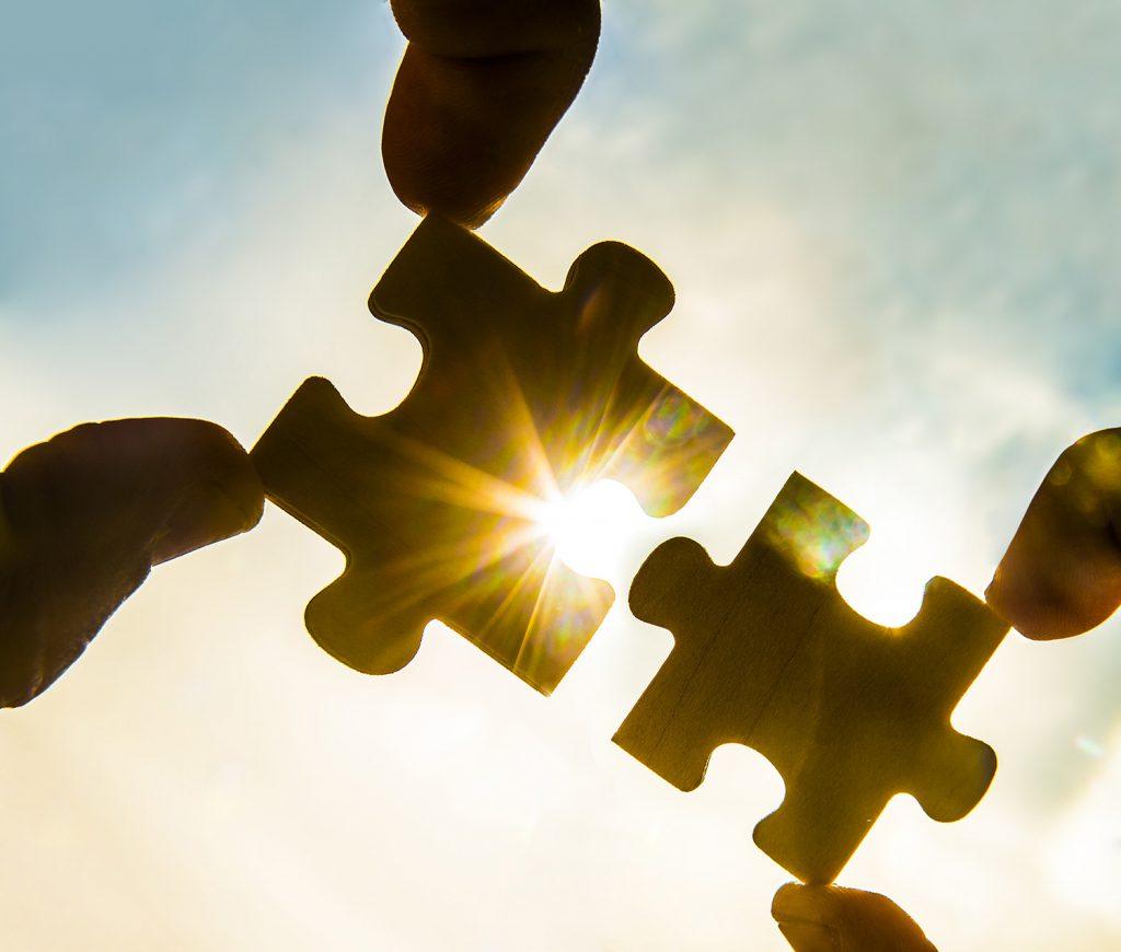 Finger halten zwei Puzzleteile zusammen in die Sonne